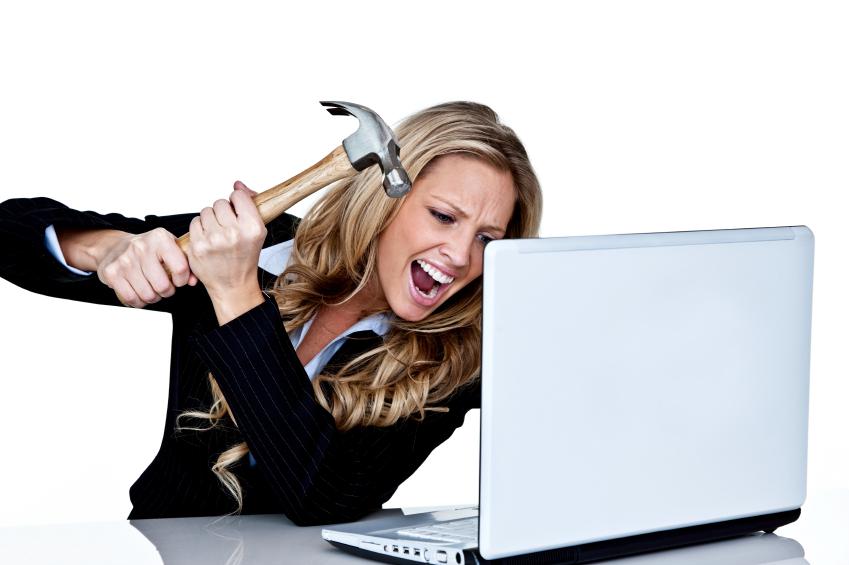 Frau die mit einem Hammer auf einen Laptop einschlägt