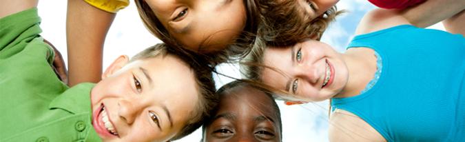 Kinder die sich zueinander beugen und ihre Arme über die Schultern der anderen Legen.